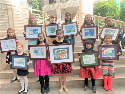 FCS Art Students Holding Framed Artwork