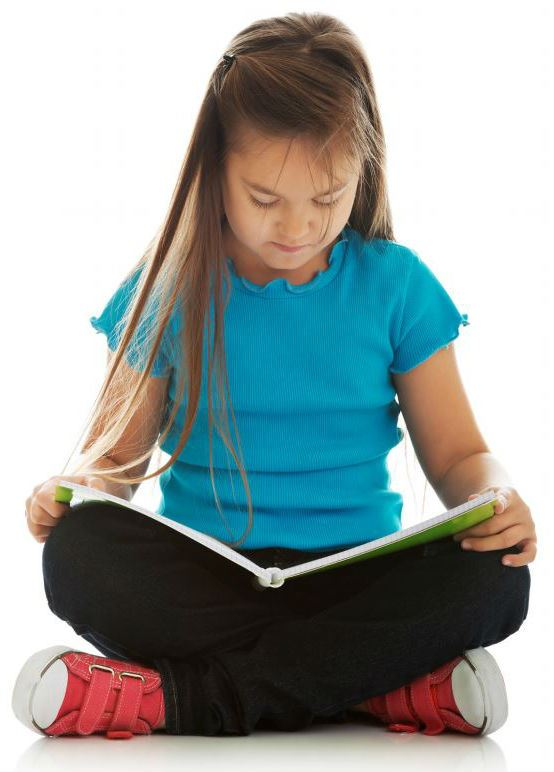 A young girl reading a notebook